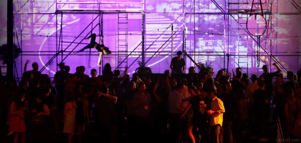 Attendees mingle during an acrobatic performance at the Over The Top Party hosted by Playtika at Casual Connect Tel Aviv 2015.
